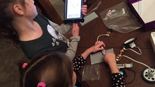 Kids follow tips on their device to begin building.