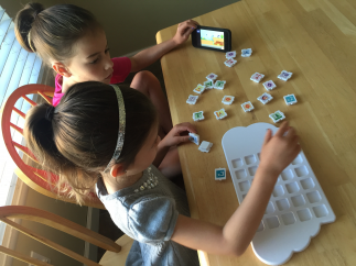 Kids build a program out of real Puzzlet pieces in the Play Tray.