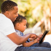 man and young son on a tablet