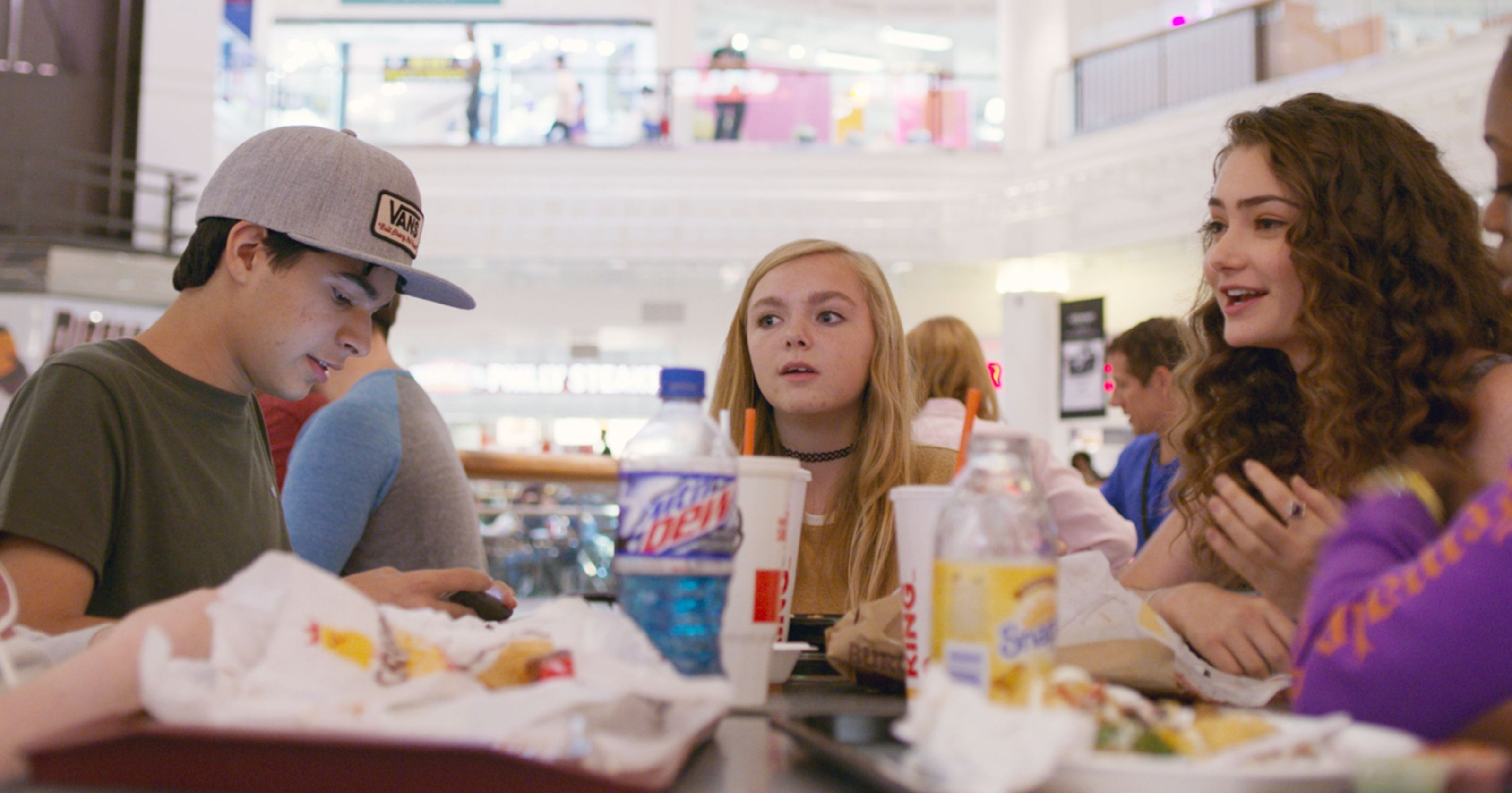 Kayla talking with high school kids in a mall food court.