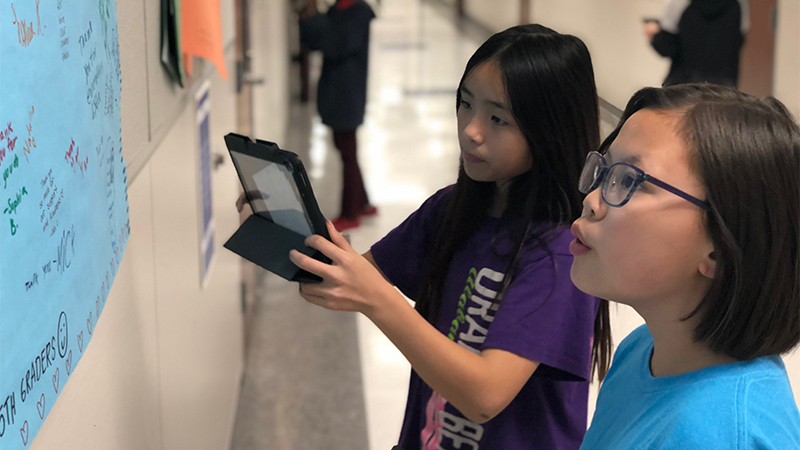 Two students using tablet in school hallway